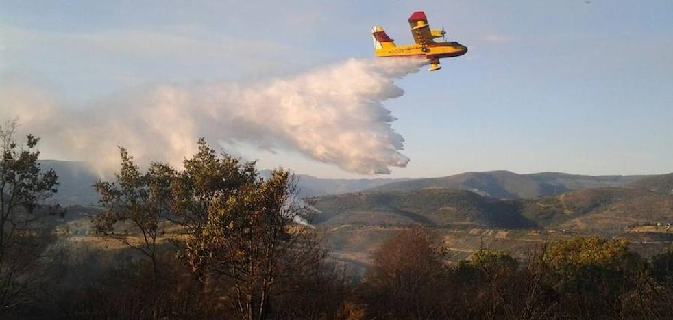 Un helicóptero y varios medios terrestres trabajan en un incendio forestal activo en Toreno