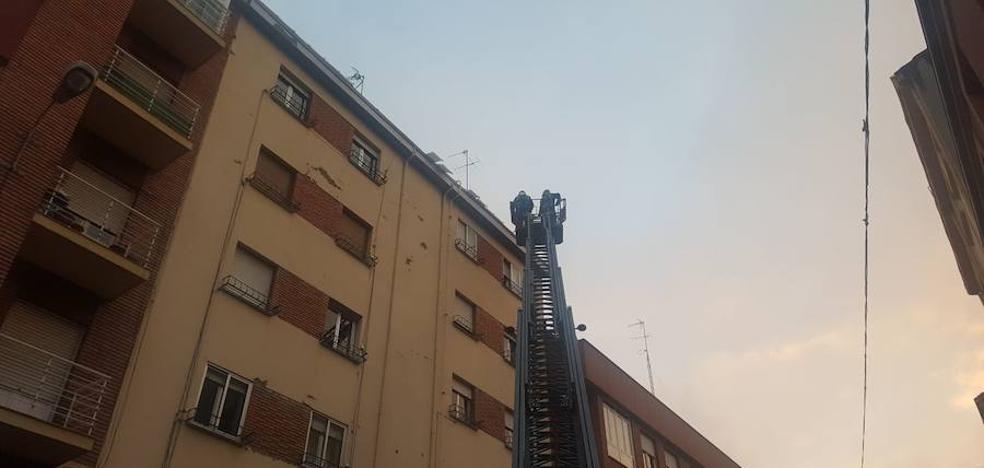 Los Bomberos cortan la calle López de Fenar para poder retirar placas de hielo de los tejados