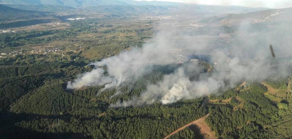 Medios aéreos y terrestres tratan de extinguir un incendio forestal en Castropodame