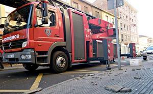 Los Bomberos de León retiran cascotes desprendidos de un edificio en la calle Burgo Nuevo