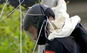 Un paracaidista se queda enganchado en una farola durante el desfile de las Fuerzas Armadas